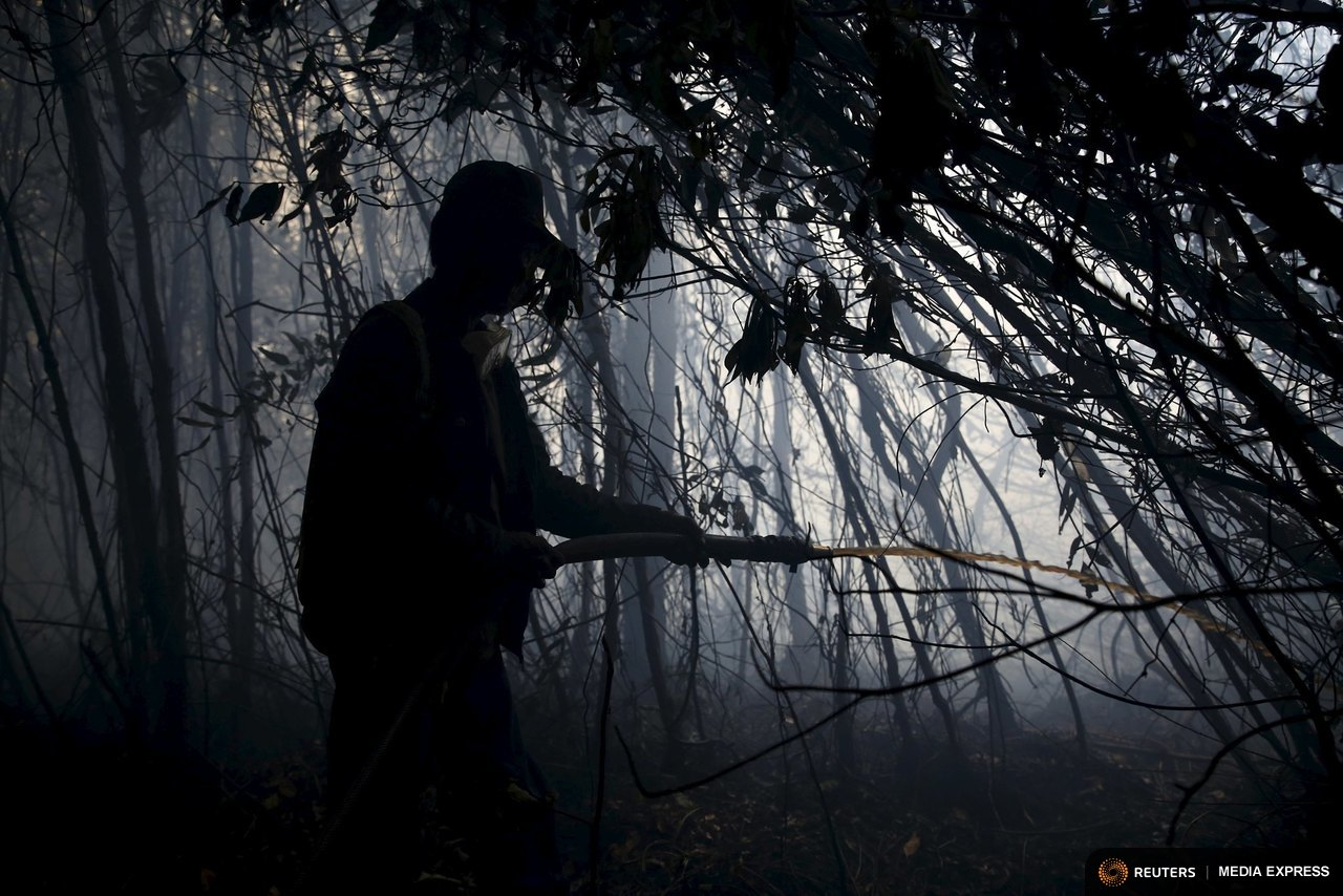 REFILE - CORRECTING NUMBER OF TROOPS A workers sprays water to extinguish fire inside a forest at the Pulo Geronggang village in Ogan Komering Ilir district in Indonesia's South Sumatra province, September 11, 2015. Indonesia said on Friday it will send more than 1,000 troops to fight fires in southern Sumatra, as smoke makes thousands sick, delays flights and pushes air quality to unhealthy levels in neighboring Singapore and Malaysia. REUTERS/Beawiharta