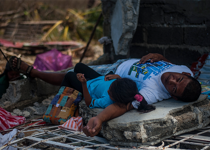 A Philippine resident and his daughter lay on a concrete slab in the aftermath of Typhoon Haiyan. The George Washington Carrier Strike Group is supporting the 3rd Marine Expeditionary Brigade in assisting the Philippine government in Operation Damayan.