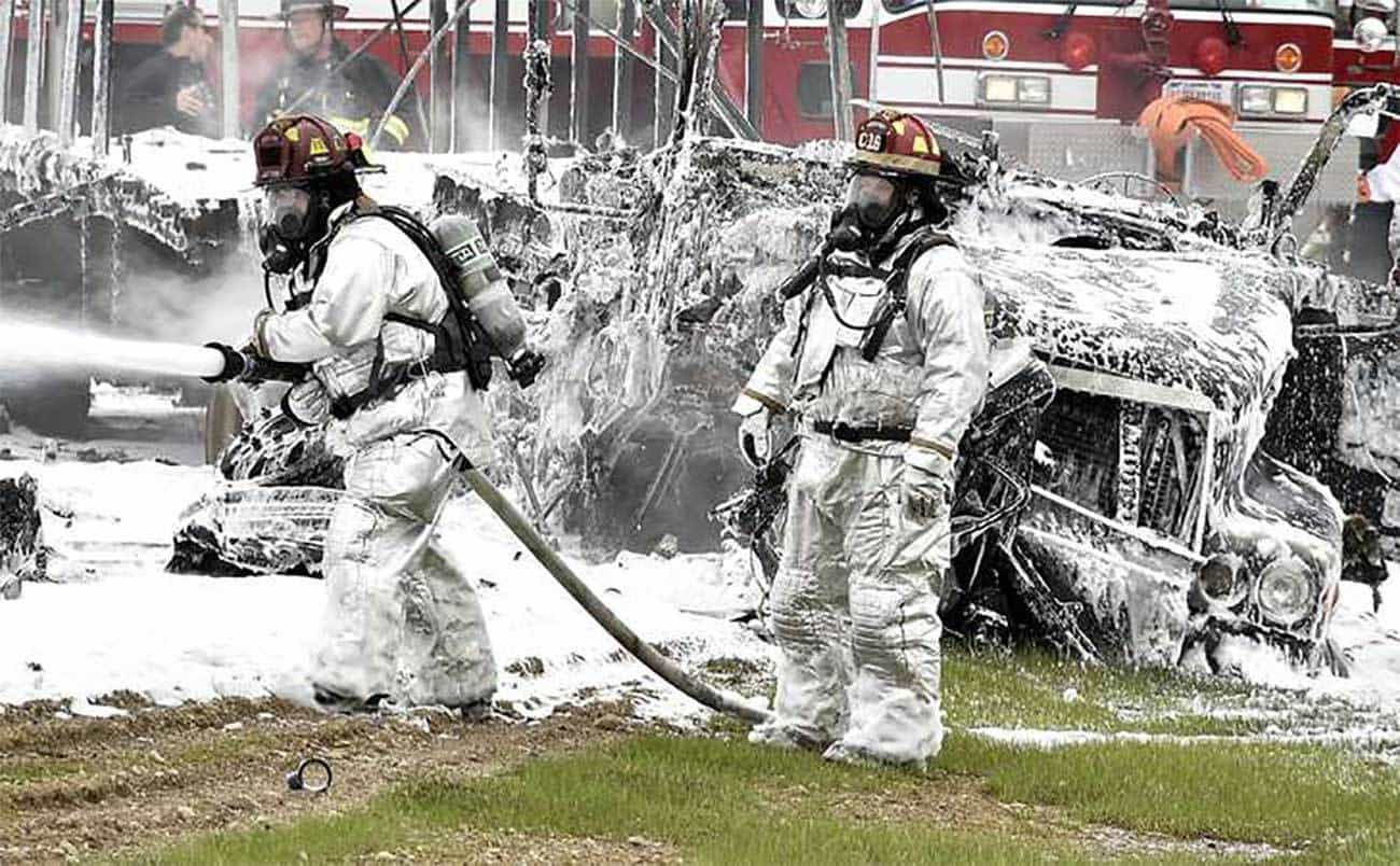 Members of the Wright Patterson fire department spray foam on a tractor trailer and car after they collided head-on and burst into flames April 14, 2015, on eastbound I-70 near the Enon Road entrance. The driver of the car, Christopher Coleman of Xenia, was killed in the crash but the truck driver escaped without injury. Bill Lackey/Staff